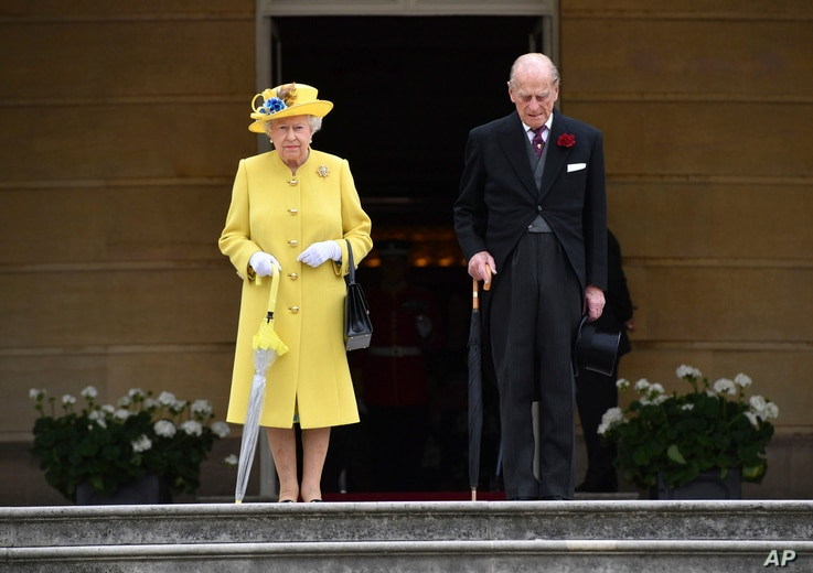 Britain's Queen Elizabeth and Prince Philip observe a minute's silence, at the start of a garden party at Buckingham Palace in London,  May 23, 2017.
