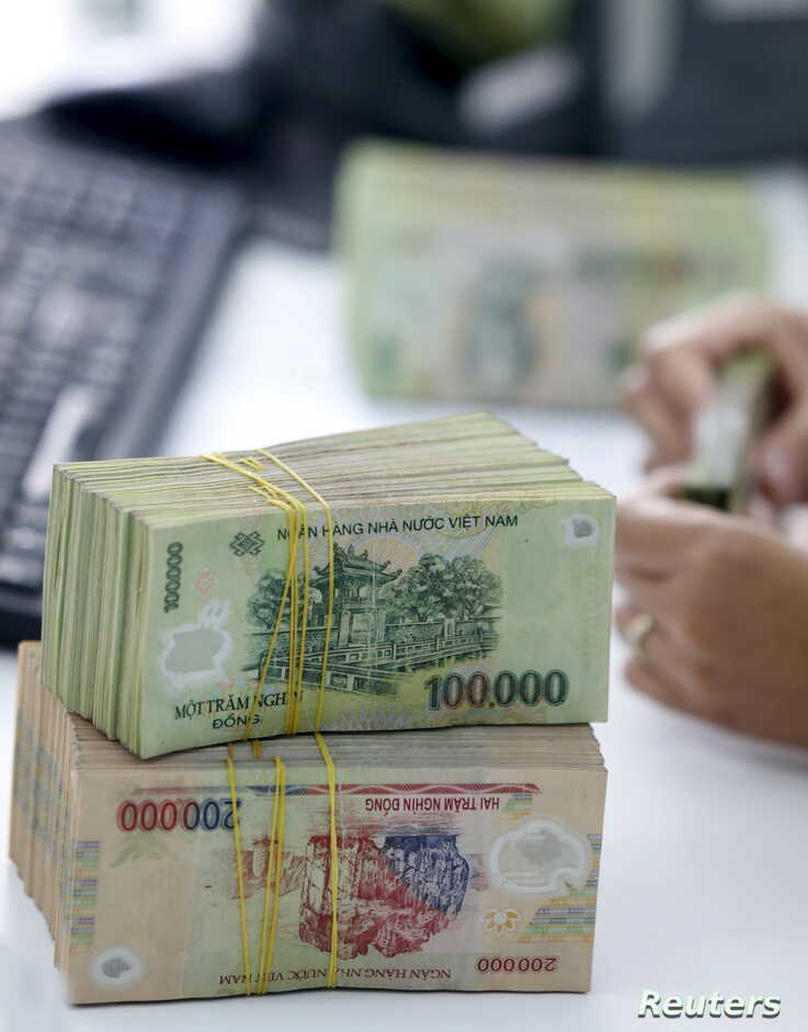 A bank employee checks Vietnamese dong banknotes at a bank in Vinh Yen city, Vietnam - RTX1ORAF