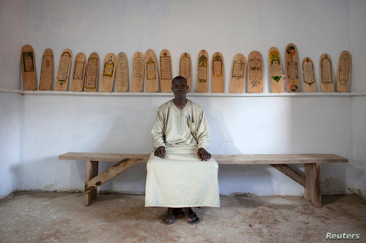 Aboubakar Yaro, head of conservation at the Djenne Library of Manuscipts, poses for a picture next to Koranic scripts written on pieces of wood in Djenne, September 1, 2012. Djenne is thought to have at least 10,000 manuscripts held in private collec...