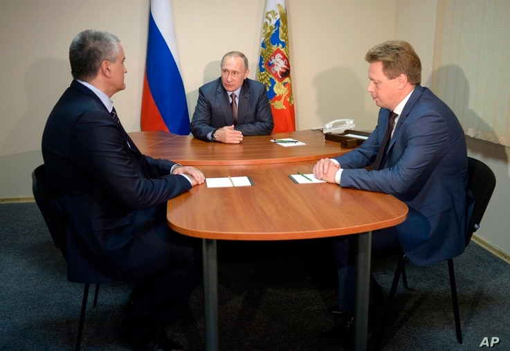 Russian President Vladimir Putin, center, meets with Crimean leader Sergei Aksyonov, left, and acting Sevastopol governor Dmitry Ovsyannikov, while visiting the youth educational forum 'Tavrida' in the Bakal Spit in Crimea, Aug. 19, 2016.