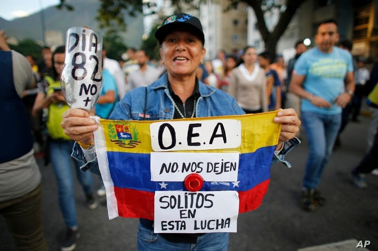 """A demonstrator holds up a Venezuelan national flag with a message that reads in Spanish; """"OAS, don't leave us alone in this fight"""", in Caracas, Venezuela, June 21, 2017."""