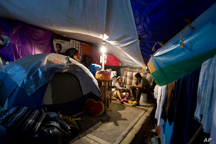 Axel Lopez Martinez, 18, helps 13-year-old neighbor Juan Alfredo Cuaclayo Rodriguez with his homework inside one of the tent camps where residents of earthquake-damaged Independencia 18 have been living, in Mexico City, March 14, 2018.