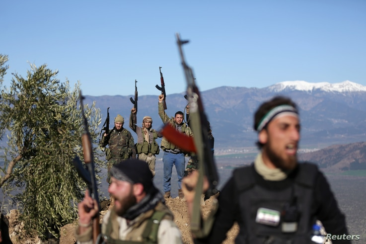 Turkish-backed Free Syrian Army fighters react as they hold their weapons near the city of Afrin, Syria, Feb. 19, 2018.