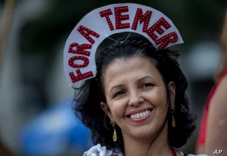 """A reveler wears a crown that reads in Portuguese: """"Out Temer"""" during a carnival street party in Rio de Janeiro, Feb. 24, 2017. Merrymakers took to the streets to protest Brazil's President Michel Temer."""