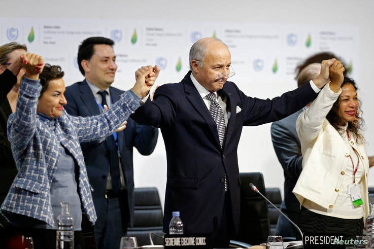 French Foreign Affairs Minister Laurent Fabius (C), President-designate of COP21 and Christiana Figueres (L), Executive Secretary of the UN Framework Convention on Climate Change, hold hands during the final plenary session at the World Climate Chang...