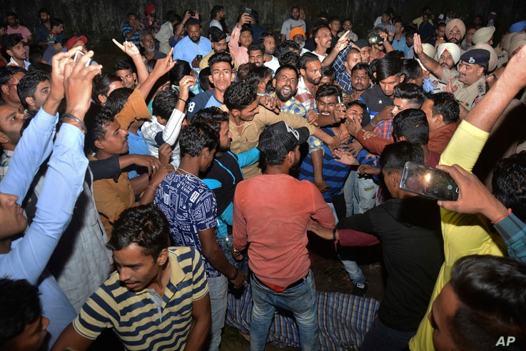 An angry crowd shouts slogans beside the body of a victim of a train accident in Amritsar, India, Oct. 19, 2018.