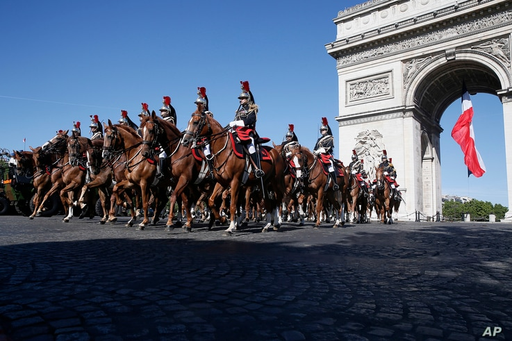 French Republican Guards ride their horses past the Arc de Triomphe in Paris, July 14, 2017. The annual Bastille Day parade is being opened by American troops with President Donald Trump as the guest of honor to commemorate the 100th anniversary of t...