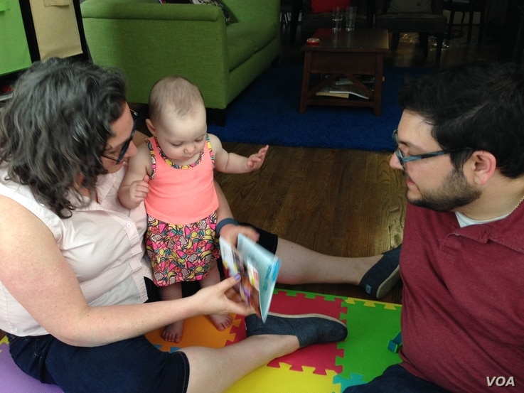Rob and Jessica Lott enjoy spending time with their 11-month old daughter Shulie, June 10, 2016. (J. Taboh/VOA)