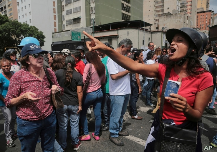 A government supporter holds a copy of Venezuela's constitution as she argues with opposition members outside the Supreme Court where opposition protesters gathered to show support for the chief prosecutor's motion to stop President Nicolas Maduro's ...