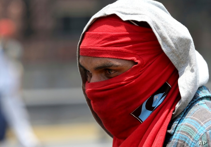 A masked demonstrators keeps his eyes on a group of Bolivarian National Guard officers during a protest in Caracas, Venezuela,  April 10, 2017.
