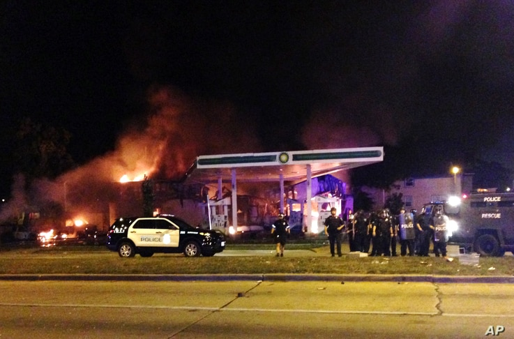 Authorities respond near a burning gas station as dozens of people protest following the fatal shooting of a man in Milwaukee, Aug. 13, 2016.
