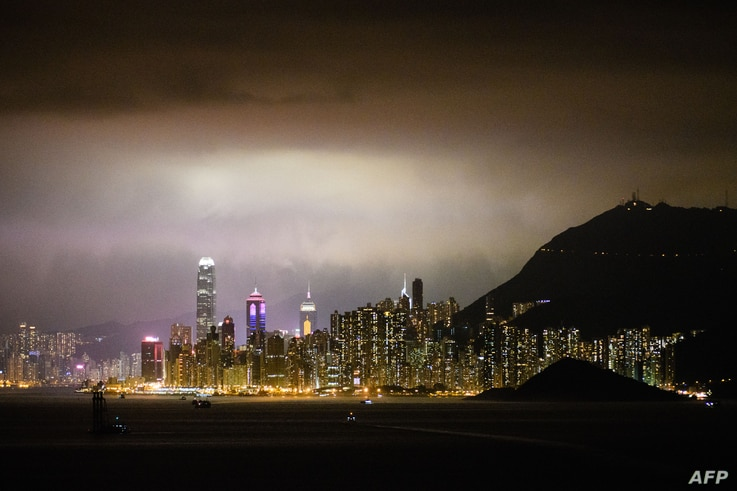 This general view taken late on February 25, 2018 shows ships sailing in the waters off Hong Kong and the city's skyline.