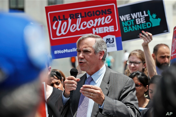 Sen. Jeff Merkley, D-Ore., speaks as protesters hold up signs and call out against the Supreme Court ruling upholding President Donald Trump's travel ban in front of the Supreme Court,  June 26, 2018 in Washington.