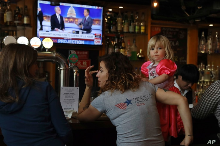 Christine Fox and her daughter Emmylou Fox from Washington state wait for the results of the U.S. midterm elections during a gathering organized by Democrats Abroad in Beijing, China, Nov. 7, 2018.