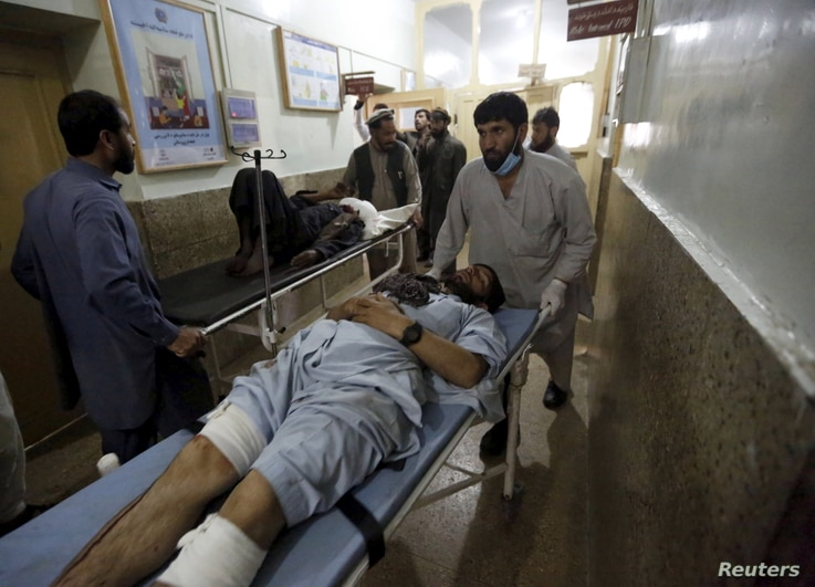Injured men are brought in for treatment at a hospital after a suicide attack in Asadabad, capital of Kunar province, Afghanistan February 27, 2016. A suicide bomber killed an Afghan militia commander and at least 10 others in the eastern province of...