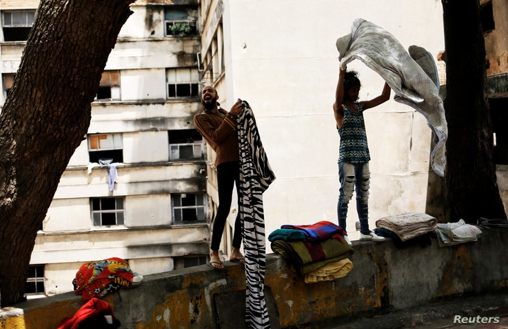 Rodrigo (left), 26, and Wam, 24, who are among members of lesbian, gay, bisexual and transgender (LGBT) community, that have been invited to live in a building that the roofless movement has occupied, shake blankets, in downtown Sao Paulo, Brazil, No...