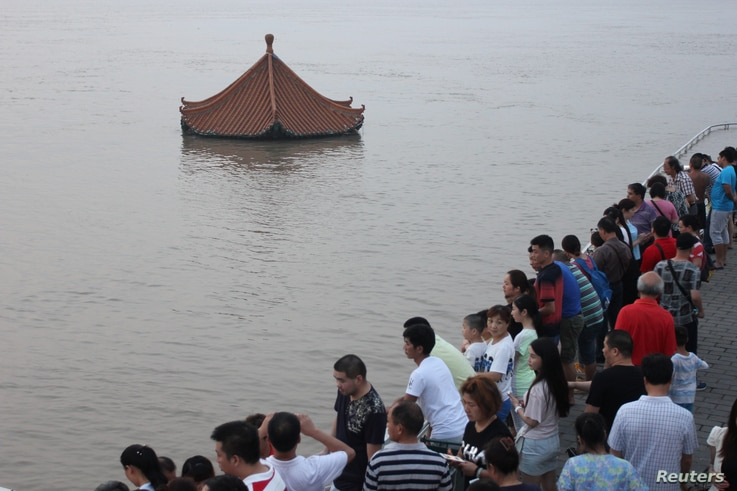 People watch a submerged pavilion in the flooded Yangtze River in Wuhan, Hubei province, July 7, 2016. (Reuters)