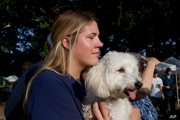 Heidi Guillory hugs her dog Cohen during a moment of silence for shooting victims in Lafayette, La., July 25, 2015.