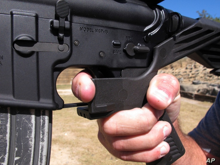 FILE - In this Oct. 4, 2017 file photo, shooting instructor Frankie McRae demonstrates the grip on an AR-15 rifle fitted with a bump stock at his 37 PSR Gun Club in Bunnlevel, N.C.