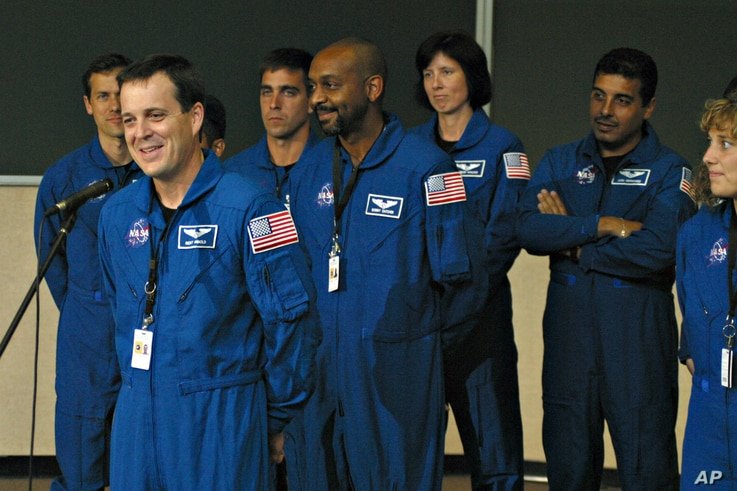 FILE - Ricky Arnold, left, speaks after being sworn in during a ceremony inside the old Apollo Mission Control room at Johnson Space Center in Houston, Texas, June 14, 2004.