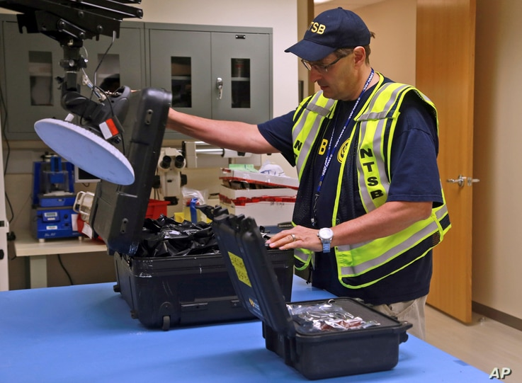 FILE -- National Transportation Safety Board engineer William Tuccio on October 4, 2016, removes the event recorder memory board and video recorder hard drive, recovered from the N.J. Transit train that  crashed into a New Jersey rail station.