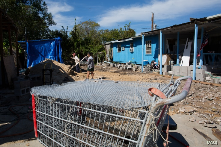 The Le family spends a Saturday afternoon cleaning the lot of their flood-damaged mobile home, which has since been replaced.