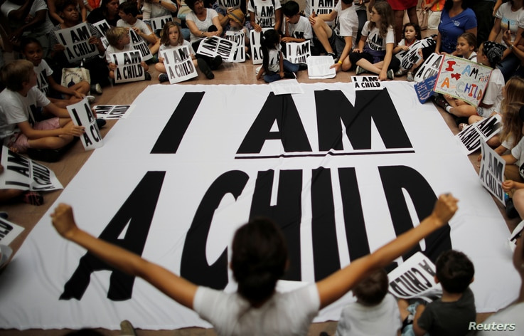 """Children and family members take part in a sit-in following a march to mark """"the court-ordered deadline for the Trump Administration to reunify thousands of families separated at the border, in Washington, U.S."""