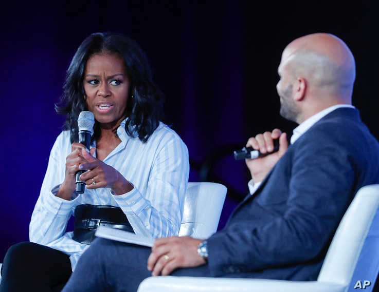 Former first lady Michelle Obama talks with Sam Kass, former White House Chef and Senior Policy Adviser for Nutrition, at the Partnership for a Healthier American 2017 Healthier Future Summit in Washington, May 12, 2017