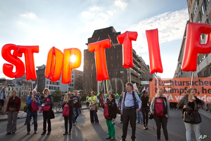 Protesters hold an anti-TTIP inflatable banner during a demonstration against international trade agreements in Brussels, Sept. 20, 2016.