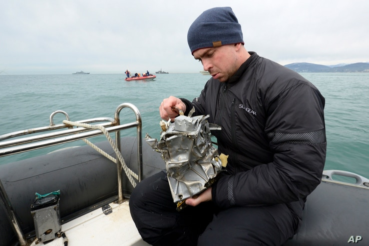 A Russian Emergency Ministry diver inspects a fragment of a plane recovered from the Black Sea, outside Sochi, Russia, Dec. 27, 2016.