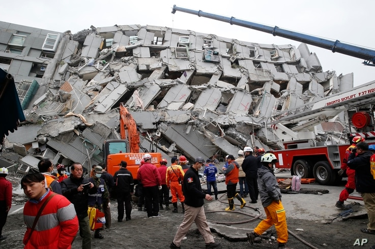 Rescue workers search a collapsed building from an early morning earthquake in Tainan, Taiwan, Feb. 6, 2016.