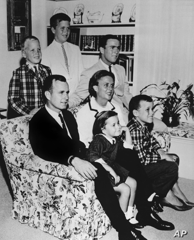FILE - In this 1964 file photo, George H.W. Bush sits on couch with his wife Barbara and their children. George W. Bush sits at right behind his mother. Behind couch are Neil and Jeb Bush.