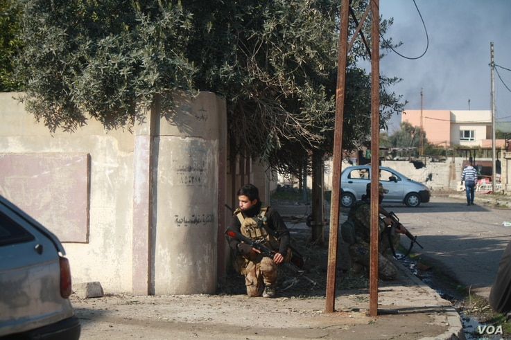 Iraqi soldiers peers around a corner to a road in range of IS sniper fire from across the river.  Locals say as Iraqi forces take back areas, life is starting to go back to normal in many parts of eastern Mosul, Jan. 29, 2017. (H. Murdock/VOA)