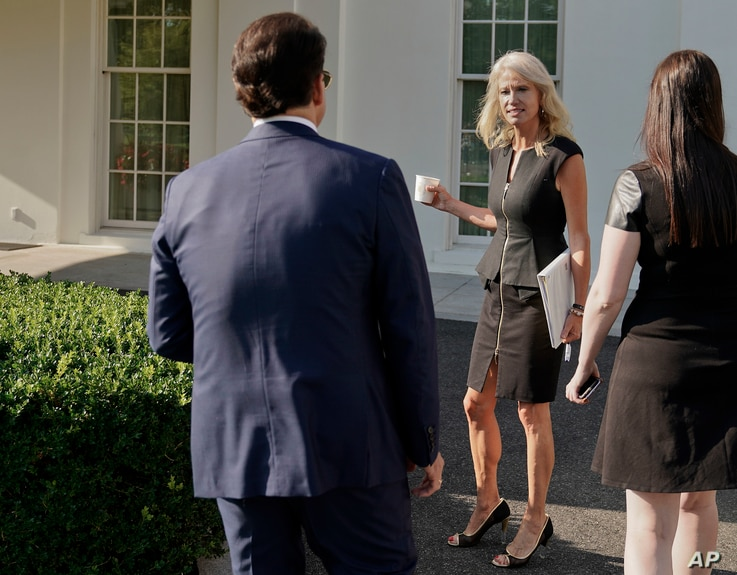 FILE - Counselor to the President Kellyanne Conway, center, waits for White House communications director Anthony Scaramucci, left, outside the West Wing of the White House in Washington, July 26, 2017.