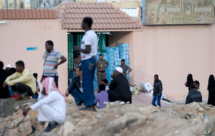 FILE - Saudi security forces watch Ethiopians gather as they wait to be repatriated in Manfouha, southern Riyadh, Nov. 13, 2013.