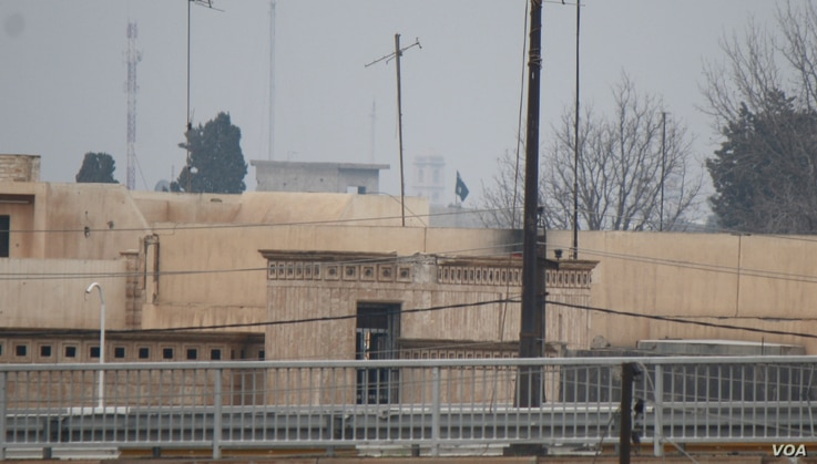 From a rooftop in western Mosul, an Islamic State flag can be seen waving in the militant-controlled area in Mosul, Iraq, March 2, 2017. (H. Murdock/VOA)