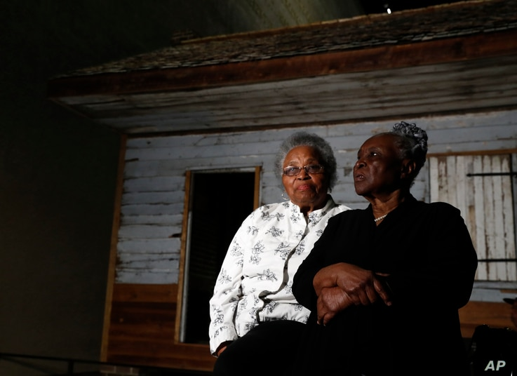 Emily Meggett, left, and Isabell Meggett Lucas sit together at the National Museum of African American History in Washington, April 11, 2017, in front of a slave cabin on display. Lucas was born in the two-room wood cabin that dates to the 1850s.
