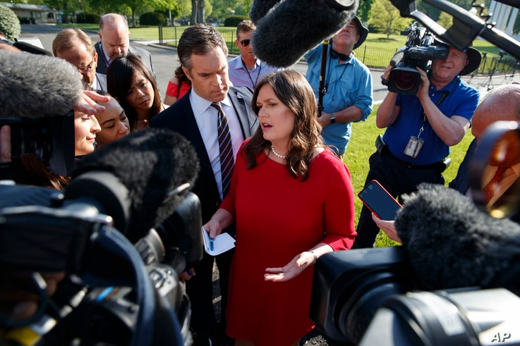 FILE - White House press secretary Sarah Sanders talks to reporters outside the White House, May 3, 2018.