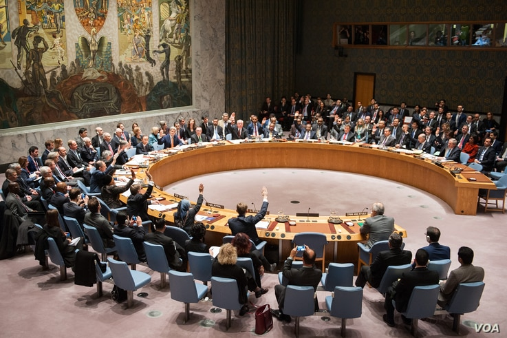 U.S. Secretary of State John Kerry and foreign leaders cast a vote during U.N. Security Council meeting on Syria, Dec. 18, 2015.