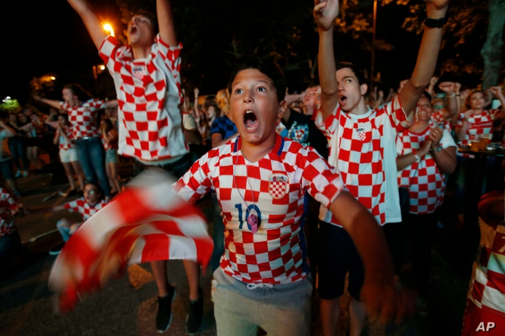 Bosnian Croats, in the streets of the southern-Bosnian town of Mostar, cheer while watching the quarterfinal match of the FIFA 2018 World Championship between Croatia and Russia, in Mostar, July. 7, 2018. The Croatian national team won the match and ...