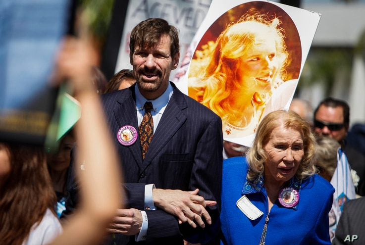 FILE - Dr. Henry Nicholas, left, leads a march with a photo of his sister Marsy Nicholas during the Orange County Victims' Rights March and Rally in Santa Ana, Calif., April 26, 2013. Nicholas is chief architect of Marsy's Law.