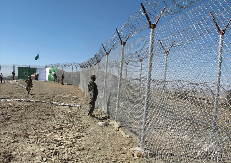 Pakistani soldiers stand guard at a fence between Pakistan and Afghanistan at Angore Adda, Pakistan, Oct. 18, 2017. Pakistan's military says the fencing and guard posts along the border with Afghanistan help prevent militant attacks.