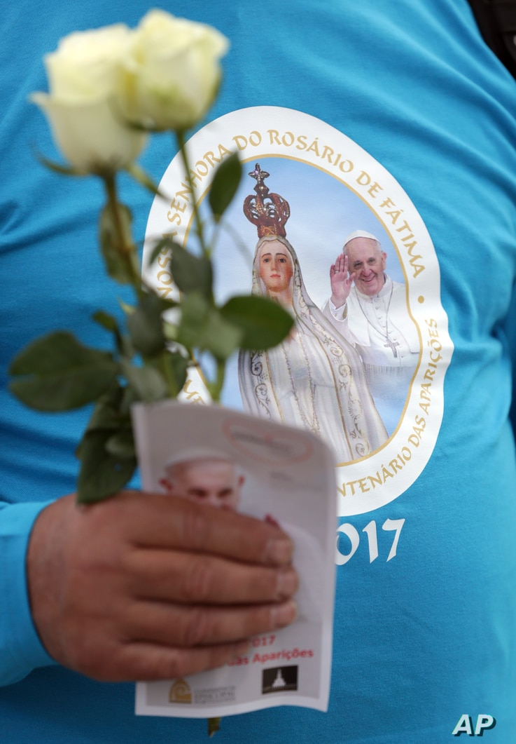 A pilgrim carrying white roses wears a T-shirt with an image of Our Lady of Fatima and Pope Francis at the Fatima Sanctuary, , May 11, 2017, in Fatima, Portugal. Pope Francis is visiting the Fatima shrine May 12-13 to canonize two Portuguese shepherd...
