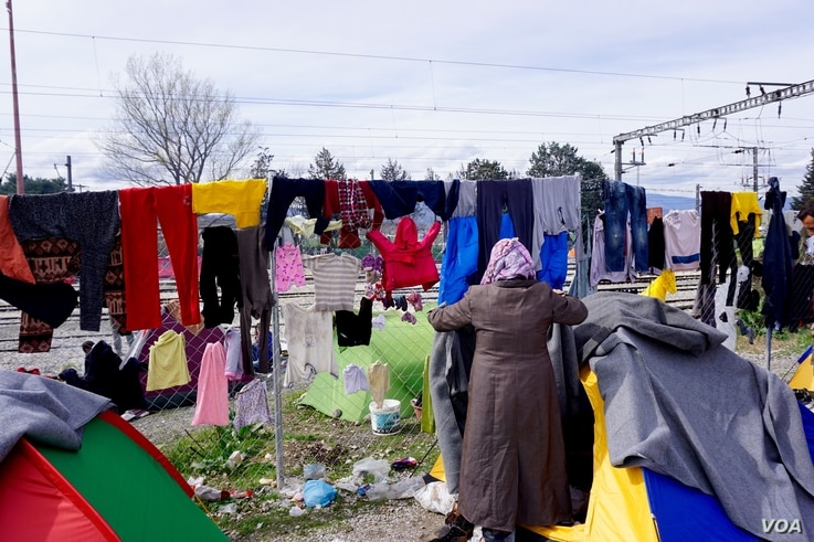 The refugees at idomeni have been soaked in several downpours this week; when the rain stops they try to dry-out. (J. Dettmer/VOA)