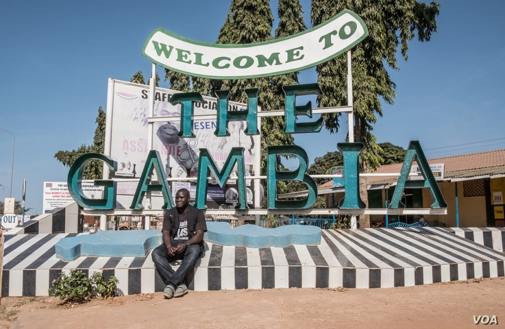 """Sheriff Junior at a """"Welcome to The Gambia"""" sign in Banjul."""