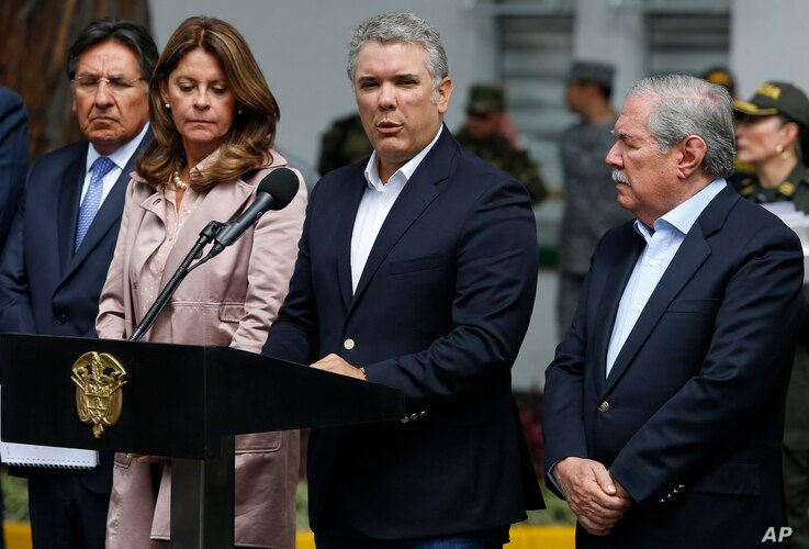 Colombia's President Ivan Duque gives a statement inside the General Santander police academy after a bomb exploded on the campus in Bogota, Jan. 17, 2019. At right is Defense Minister Guillermo Botero and at left is Vice President Martha Lucia Ramir...