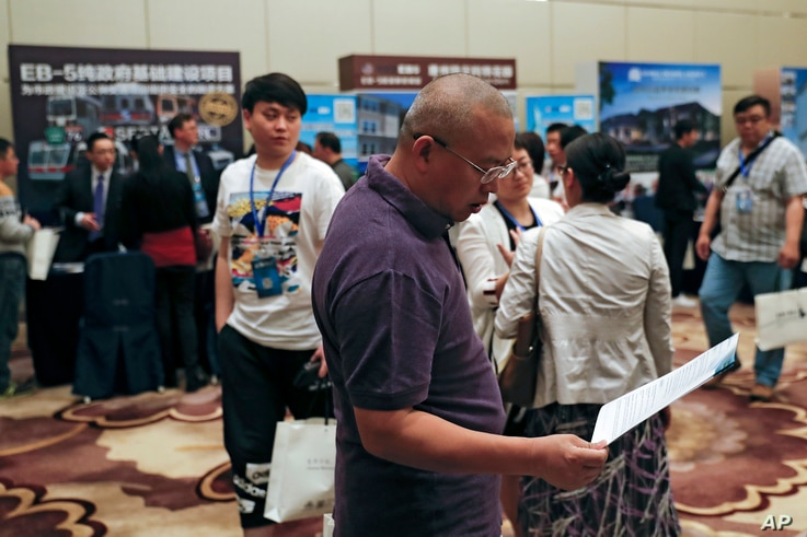 A Chinese man browses a leaflet at the exhibitor booths in a Invest in America Summit, a day after an event promoting EB-5 investment in a Kushner Companies development in Beijing, May 7, 2017. The sister of President Trump's son-in-law Jared Kushner...