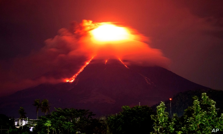 Lava cascades down the slopes of Mayon volcano as seen from Legazpi city, Albay province, around 340 kilometers (210 miles) southeast of Manila, Philippines, Monday, Jan. 15, 2018.