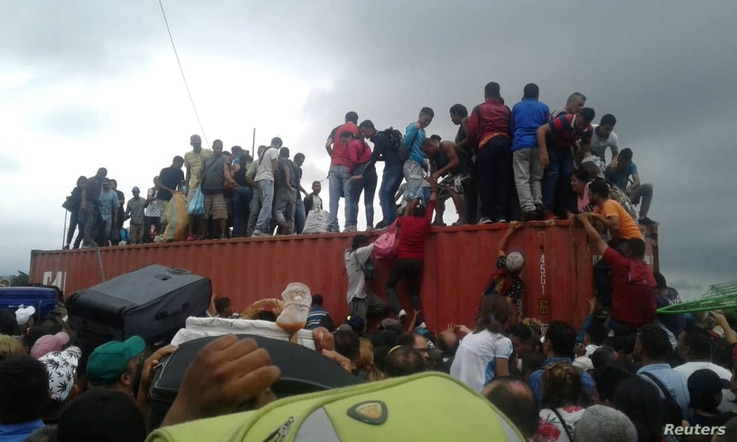 People climb atop a container used as a barricade at the Simon Bolivar international border bridge in San Antonio Del Tachira, Venezuela, April 2, 2019 in this picture obtained from social media.