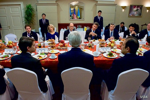 Kerry, back to camera, has a breakfast meeting with members of the American Chamber of Commerce in Kazakhstan. Executive director Doris Bradbury is among the diners facing him.